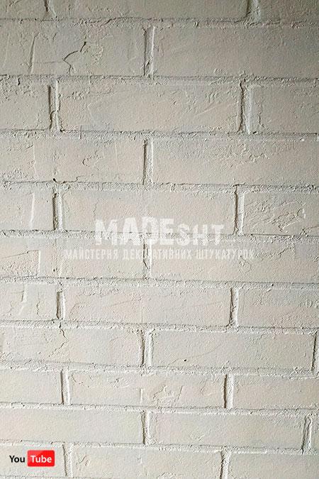Имитация кирпичной кладки окрашенной в белый цвет.